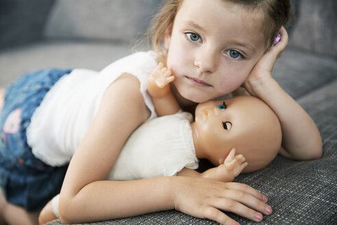 Portrait of little girl lying on sofa with her doll, close-up - JATF000391