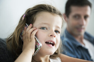 Portrait of little girl phoning with cellular, her father watching her - JATF000427