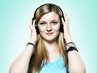 Portrait of teenage girl hearing music with headphones, studio shot - STKF000374
