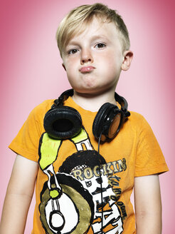 Portrait of pouting little boy with headphones, studio shot - STKF000377