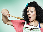 Portrait of astonished young woman with wooden spoon, studio shot - STKF000395