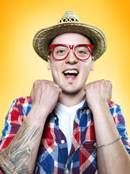 Portrait of happy young man wearing red glasses and hat, studio shot - STKF000398