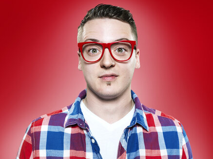 Portrait of young man with red glasses, studio shot - STKF000401