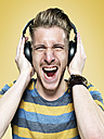 Portrait of screaming young man with headphones, studio shot - STKF000407