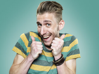 Portrait of happy young man with thumps up, studio shot - STKF000410