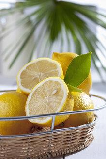 Sliced and whole lemons in basket, studio shot - CSF020175
