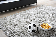 Germany, Cologne, Football and chips in front of couch - PDF000542