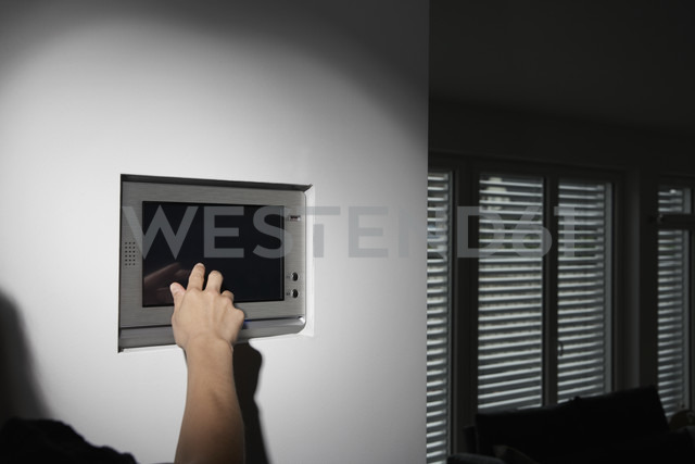 Germany, Cologne, Woman using tele control for roller blinds - PDF000570