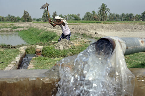 Pakistan, Punjab, village Basti Lehar Walla, man cleansing an irrigation ditch - FLK000147