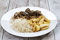 Plate with liver of beef, rice, apple wedges on white wooden table, studio shot - CSF020254