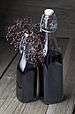 Elderberries (Sambucus) and two bottles of elderberry juice on wooden table, studio shot - CSF020264