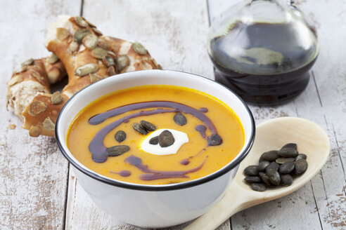 Pumpkin soup in old bowl garnished with pumpkin seed oil, pumpkin seeds and sour cream served with pretzel roll, studio shot - CSF020273