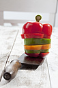 Mix of sliced sweet peppers (Capsicum) from different colours stacked on chopping knife, studio shot - CSF020292