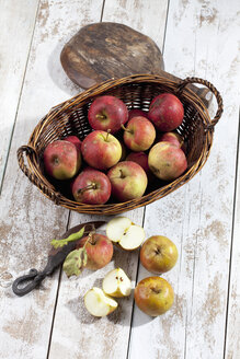 Organic apples (Malus), basket, wooden spoon and a knife on white wooden table, studio shot - CSF020301