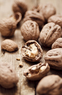 Walnuts with shell, one without, on wooden table, close-up - CZF000099