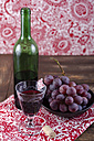 Red wine, wine glass and wine grapes on wooden table - ODF000584