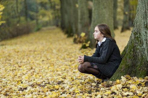 Girl crouching on a way in autumnal forest - PA000037