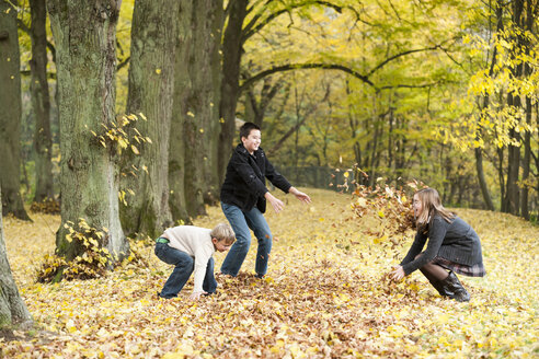 Three children throwing autumn leaves in a forest - PA000039