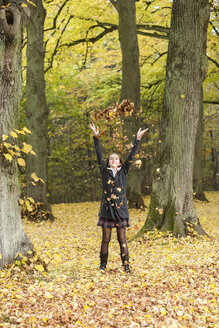 Girl throwing autumn leaves in a forest - PA000041