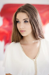 Portrait of serious looking teenage girl in front of a red painting - GDF000282