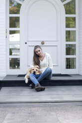 Teenage girl with dog sitting in front of an entry door - GDF000284