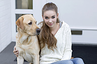 Teenage girl with dog sitting in front of an entry door - GDF000286