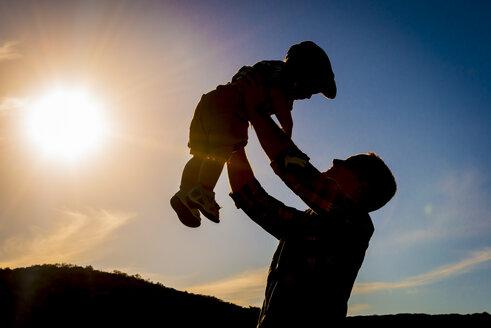 USA, Texas,Father holding son aloft - ABA001034