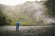 Iceland, Tourist at Skogafoss Waterfall - MBEF000763