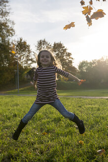 Little girl throwing autumn leaves while jumping - SAR000123
