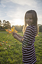 Little girl with autumn leaves in her hands standing on a meadow - SAR000124