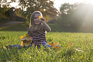 Little girl with autumn leaves sitting on a meadow - SAR000126