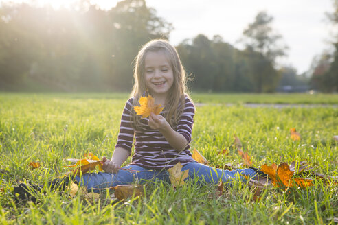 Little girl with autumn leaves sitting on a meadow - SAR000122