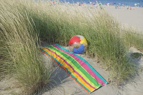 Italy, Adriatic, beach ball and towel on sand dune with grass - CRF002504