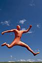 Germany, Bavaria, Man in orange zentai jumping in landscape - TCF003640