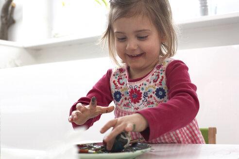 Smiling little girl painting Easter egg - FS000331