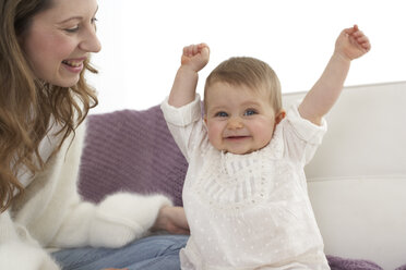 Smiling baby girl with outstrechted arms beside her mother - FSF000021