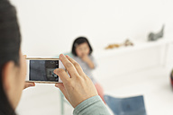 Asian woman photographing her little daughter with smartphone - FSF000064