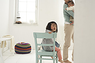 Little Asian girl sitting on a chair, mother and sister in the background - FSF000092