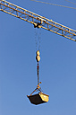 Germany, Bavaria, construction crane with container against blue sky - TCF003649