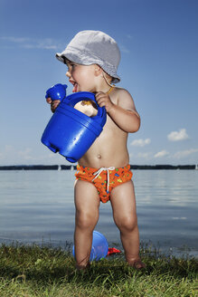 Baby boy with watering can in front of lake - RDF001199