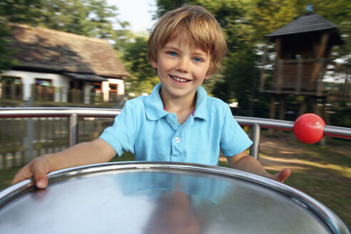 Portrait of smiling little boy on carousel at playground - RDF001230