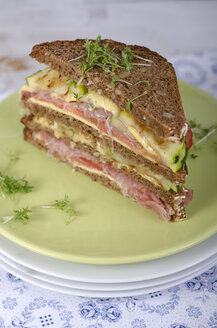 Whole-grain bread sandwich with ham, roasted zucchinis, tomatoes and cheese on plate garnished with cress, studio shot - ODF000626