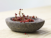 Pink peppercorns in stone bowl - SRSF000330