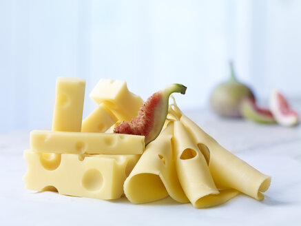 Stack of Emmentaler cheese with slices of fig on wooden table - SRSF000322