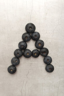 Blueberries forming letter A on sheet metal - AWDF000716