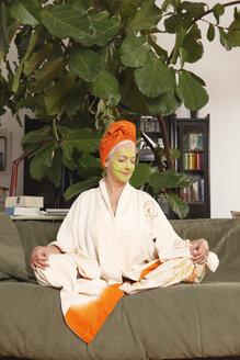 Germany, Dusseldorf, Senior woman with face mask sitting on sofa - UKF000234