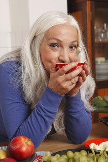 Germany, Dusseldorf, Senior woman with raw food drinking tea - UKF000236