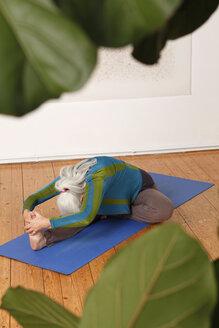 Germany, Dusseldorf, Senior woman practicing yoga - UKF000246