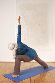Germany, Dusseldorf, Senior woman practicing yoga - UKF000247