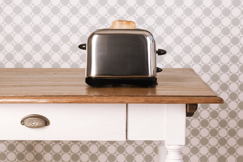 Old kitchen table with toaster and slice of bread in front of ornamental wallpaper, studio shot - DRF000269
